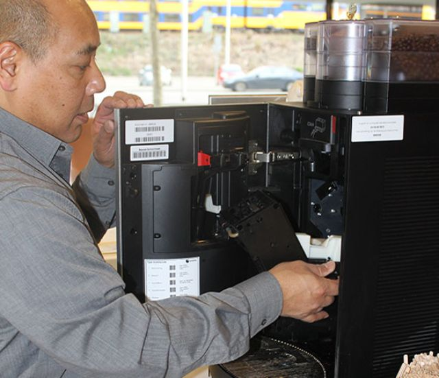 Technician performing maintenance on coffee machine